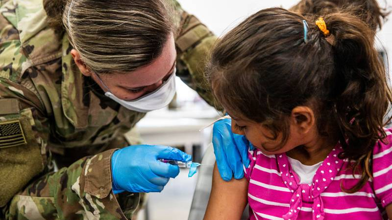 U.S. Army medical Soldiers attached to Task Force McCoy vaccinate Afghan evacuees during a...