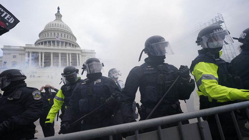 Police stand guard after holding off Trump supporters who tried to break through a police...