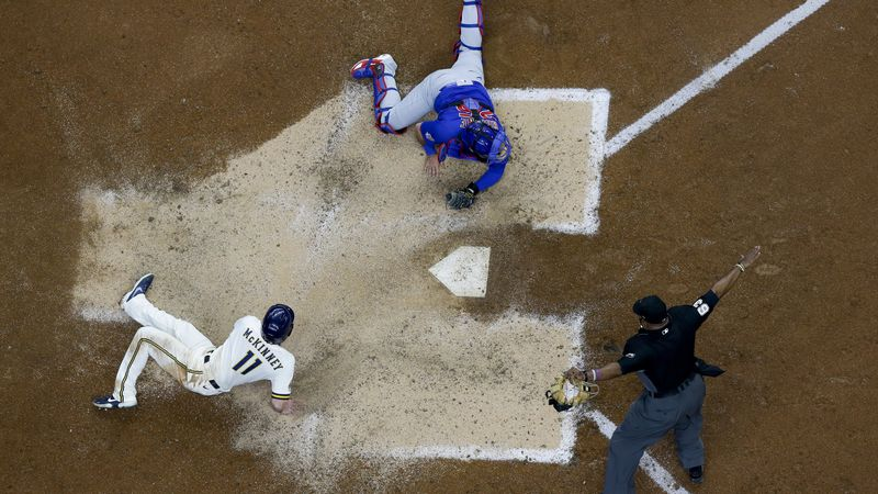 Milwaukee Brewers' Billy McKinney slides safely past Chicago Cubs catcher Austin Romine during...