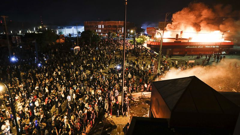 Protestors demonstrate outside of a burning Minneapolis 3rd Police Precinct, Thursday, May 28,...