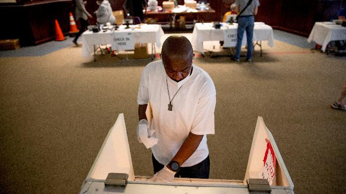 Darren Atkinson wears a mask as he wipes down a voting booth at a voting center during primary...