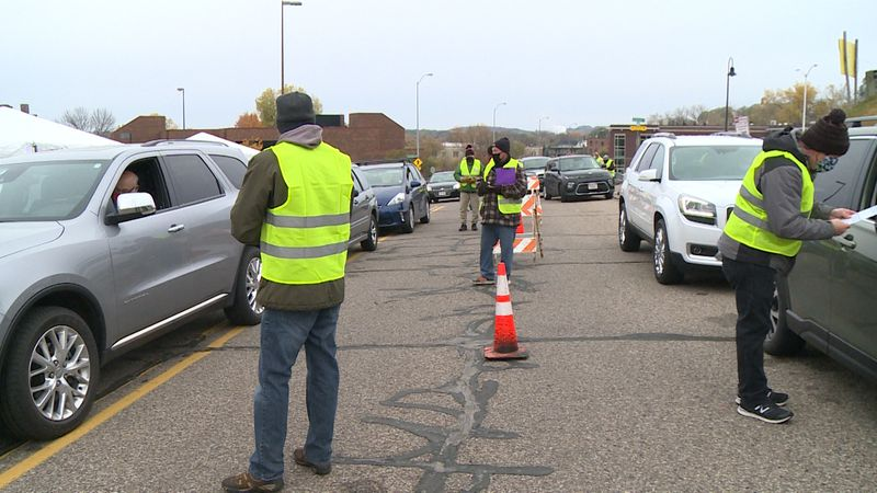Poll workers greet voters during drive-thru in-person absentee voting in Eau Claire, Wis. on...