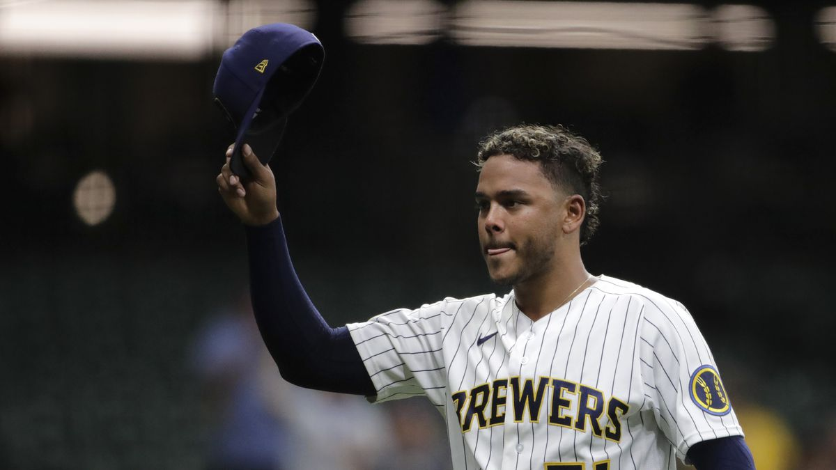 Milwaukee Brewers' Freddy Peralta tips his cap as he walks to the dugout after being removed...