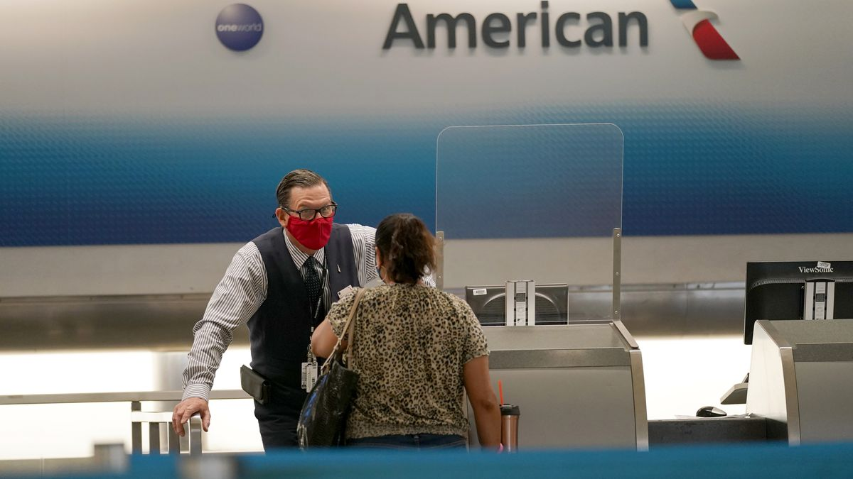 American Airlines ticket agent Henry Gemdron, left, works with a customer at Miami International Airport during the coronavirus pandemic, Wednesday, Sept. 30, 2020, in Miami. The airline industry has been decimated by the pandemic. The Payroll Support Program given to the airlines as part of the CARES Act runs out Thursday.