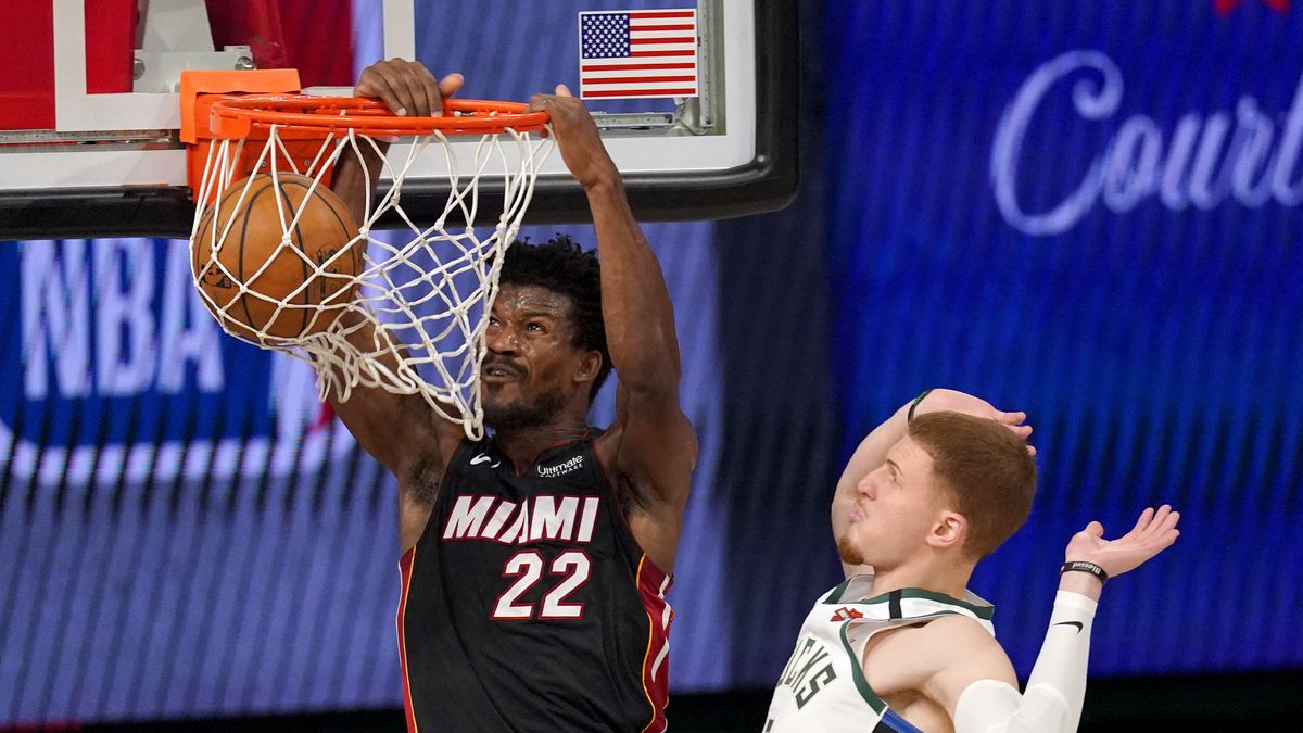 Miami Heat's Jimmy Butler (22) dunks the ball after getting past Milwaukee Bucks' Donte DiVincenzo (0) during the second half of an NBA basketball conference semifinal playoff game, Monday, Aug. 31, 2020, in Lake Buena Vista, Fla. (AP Photo/Mark J. Terrill)