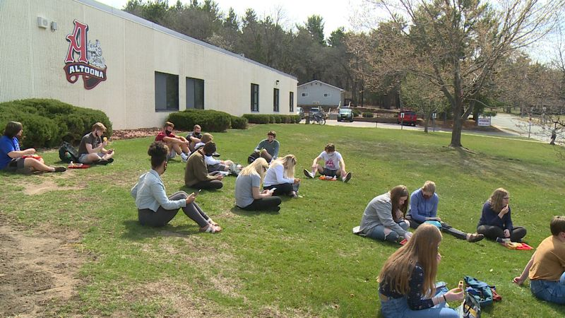 Altoona High School students sitting outside the building during their walkout in Altoona, Wis.