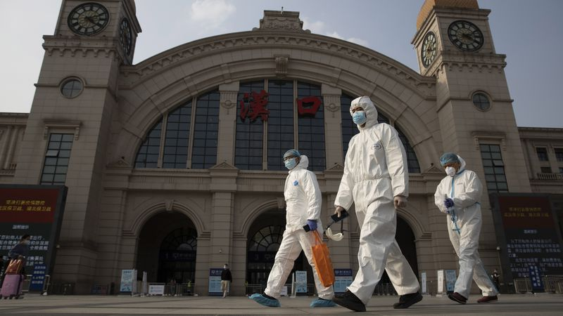 In this April 7, 2020, file photo, workers in protective suits walk past the Hankou railway...