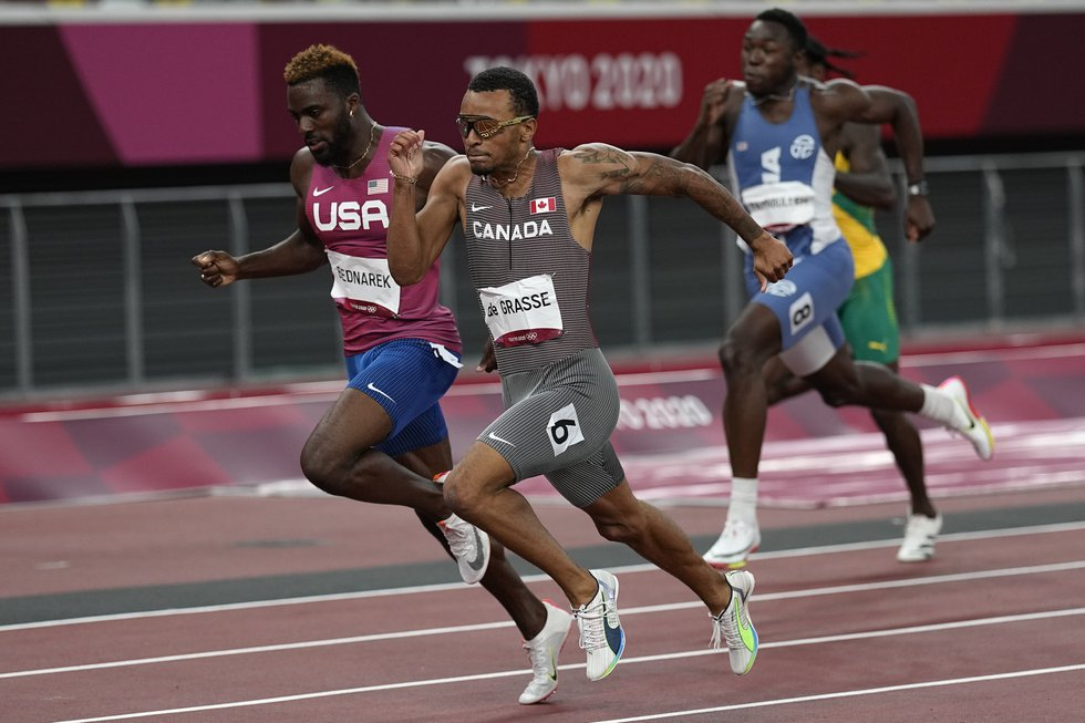 Andre De Grasse, of Canada, beats Kenneth Bednarek, left, of United States, to the line to win...