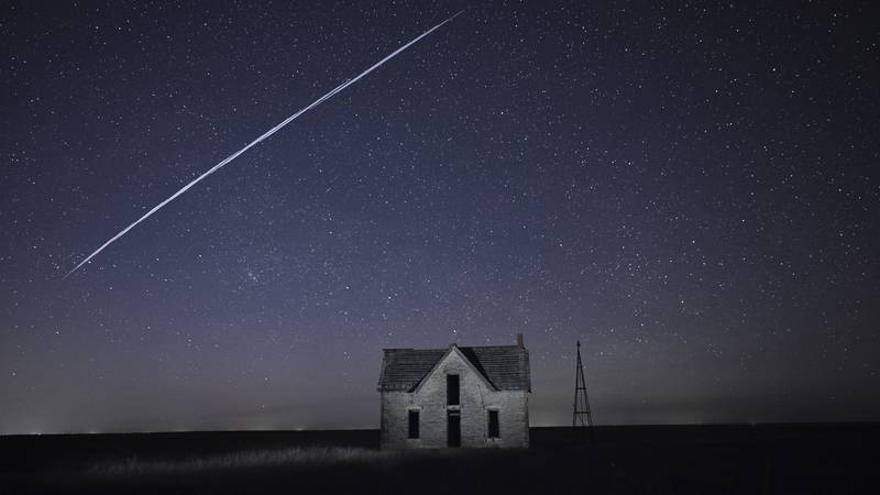 File-In this photo taken May 6, 2021, with a long exposure, a string of SpaceX StarLink...