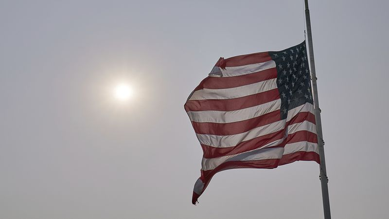 A flag flies at half staff under hazy skies due to wildfires in the west, in memory of judge...