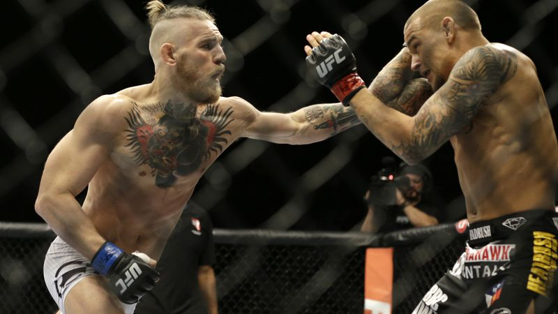 In this Sept. 27, 2014, file photo, Conor McGregor, left, and Dustin Poirier, exchange hits...