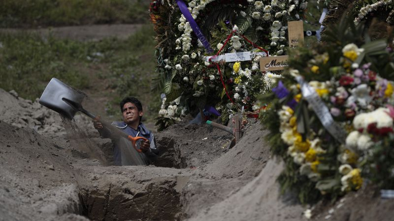 A cemetery worker digs a grave in a section of the Valle de Chalco Municipal Cemetery which...