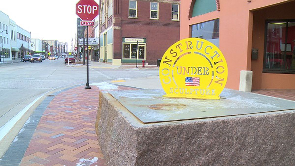 "A yellow sign stands where a sculpture called ""Stand Up for the King"" should be on the 2016 Sculpture Tour Eau Claire on Friday."
