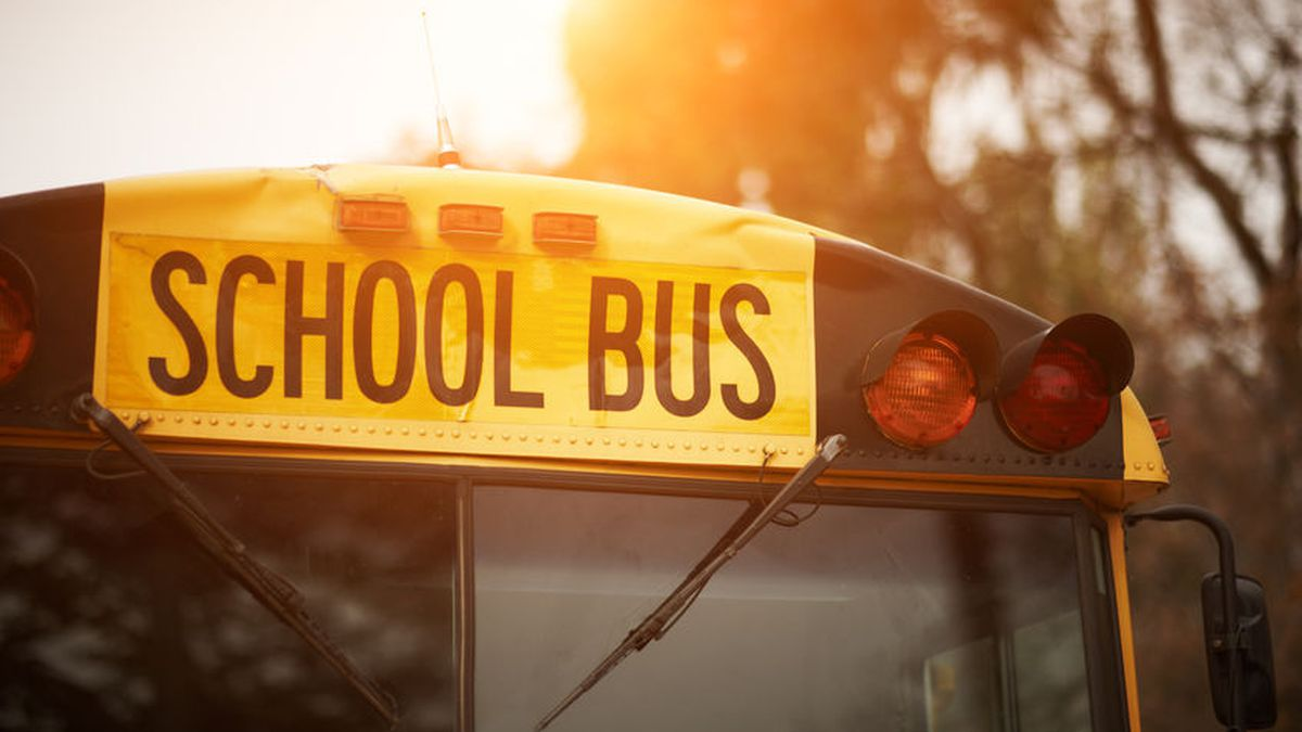 Front closeup view of yellow school bus windshield sign and lights at sunset