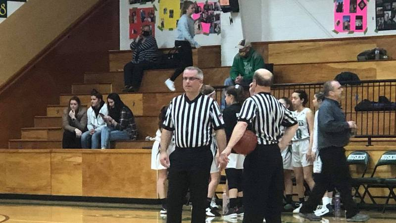 A pair of referees look on during a girls basketball game.