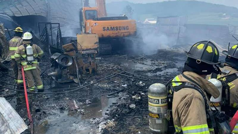 Two of three pole sheds were on fire when crews arrived Saturday morning.