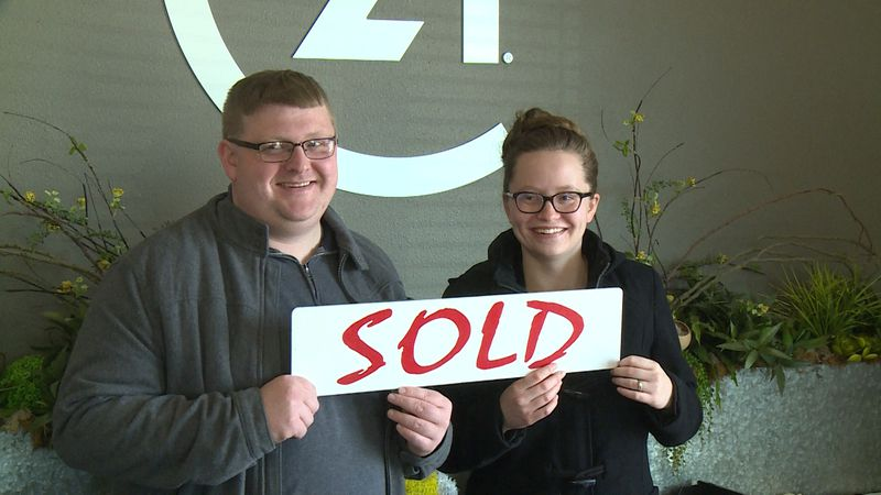 "Emma and Scott Smith holding up a ""sold"" sign at their real estate agent's office in Altoona,..."