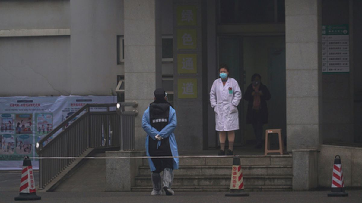 Hospital staff stand outside the emergency entrance of Wuhan Medical Treatment Center, where some infected with a new virus are being treated, in Wuhan, China, Wednesday, Jan. 22, 2020. (AP Photo/Dake Kang)