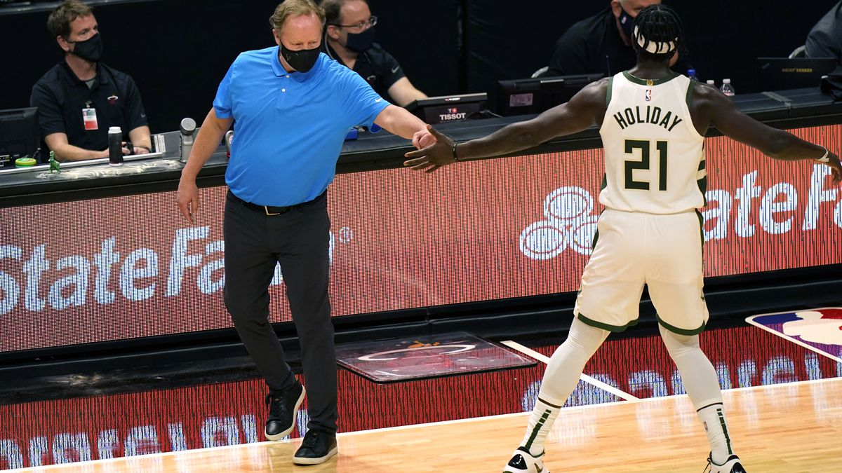 Milwaukee Bucks coach Mike Budenholzer, left, uses his fist to bump the hand of Jrue Holiday...