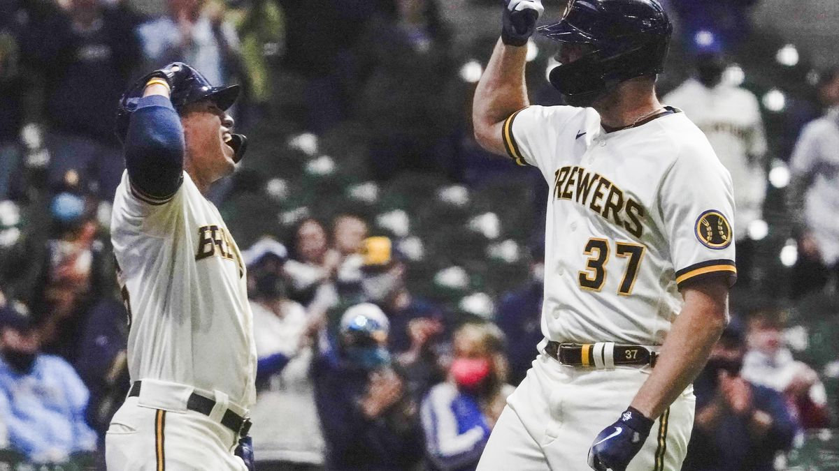 Milwaukee Brewers' Adrian Houser celebrates his home run with Tyrone Taylor during the second...