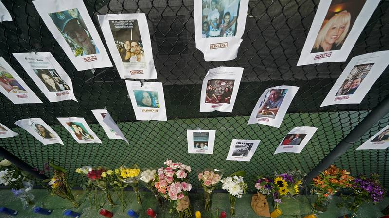 A makeshift memorial bears photos of some of the missing people that hangs from a fence, near...