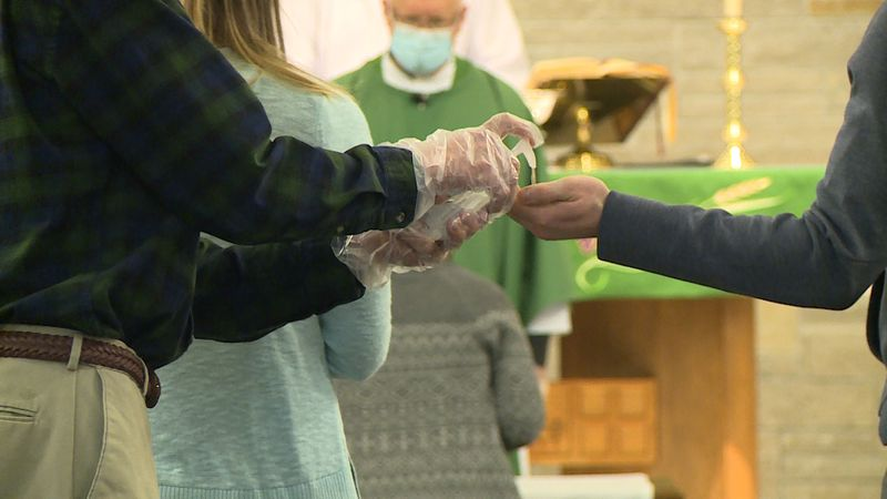 As churchgoers attend Sunday service, they must first sanitize before receiving communion at...