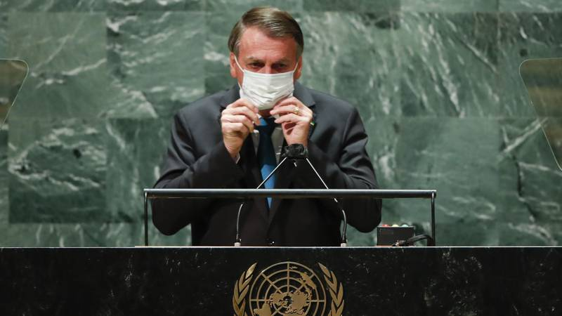 Brazil's President Jair Bolsonaro puts back on a protective face mask after speaking during the...