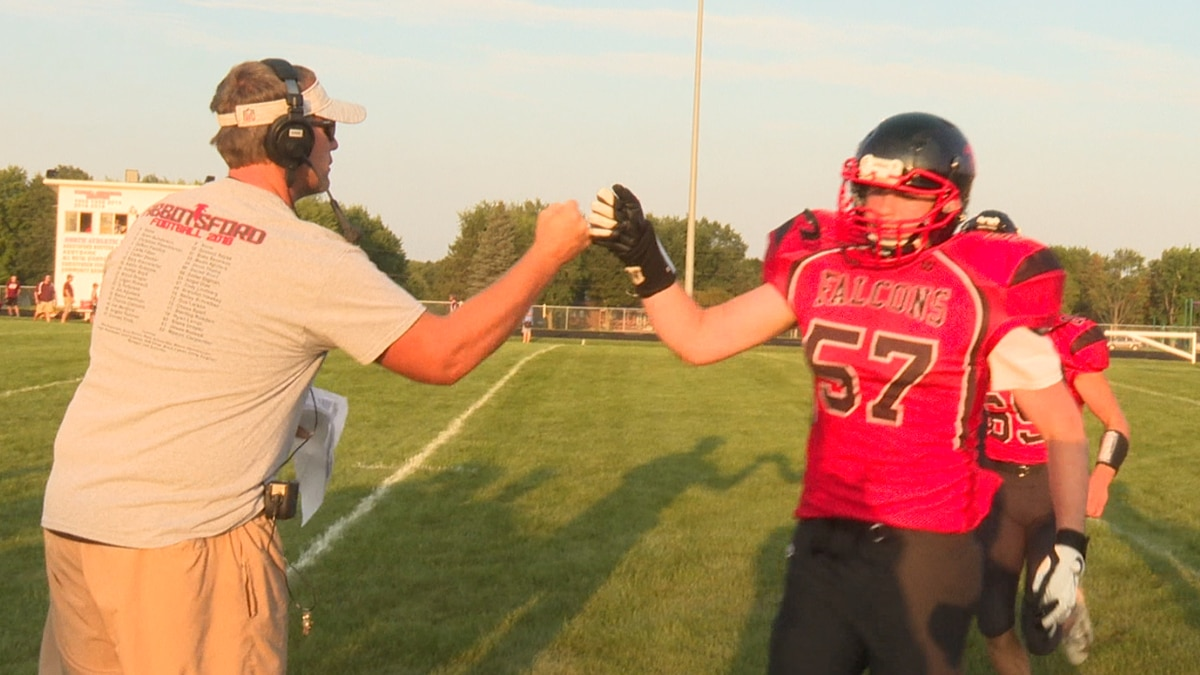 Abbotsford football coaches fist bumps players after team scores a touchdown.