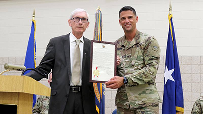 Gov. Tony Evers presents a framed proclamation to Col. John Morgen, commander of Joint Task...