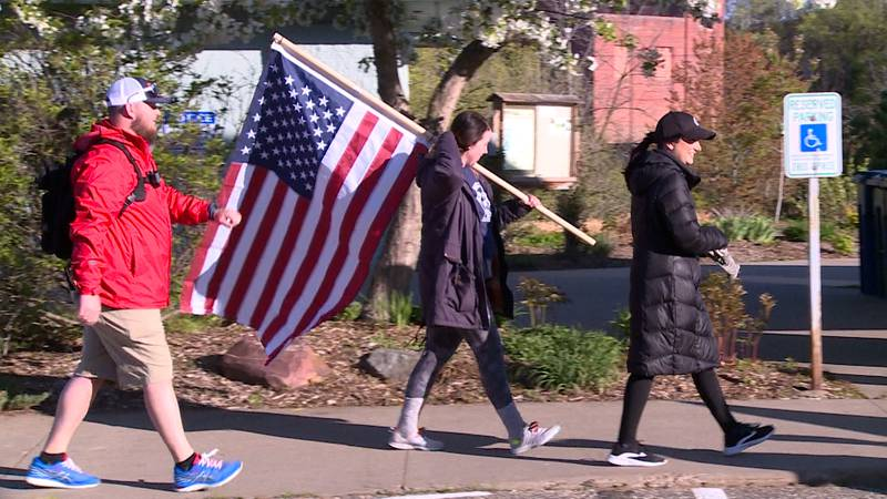People walk with flags in Eau Claire