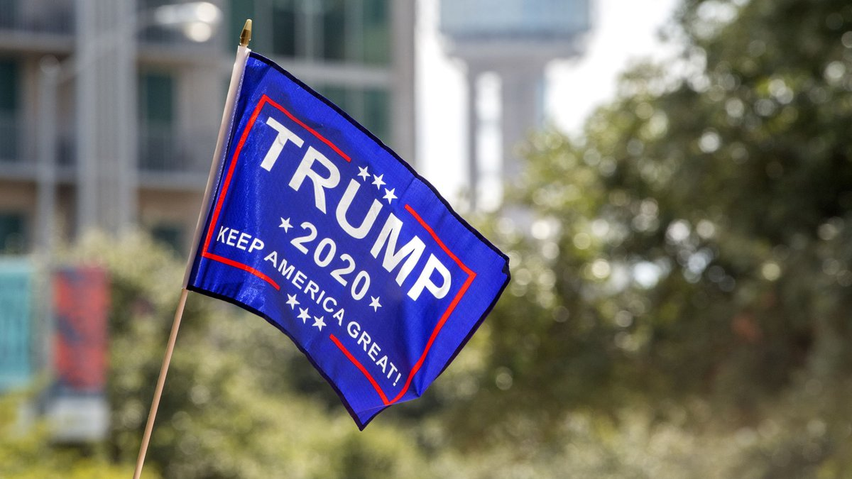 A Trump 2020 flag flies in front of Reunion Tower before a campaign rally for President Donald...