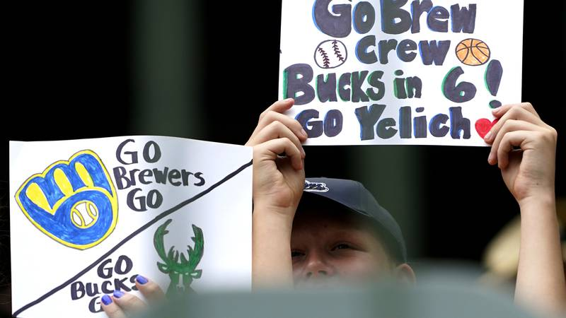 Fans hold signs before a baseball game between the Kansas City Royals and the Milwaukee...