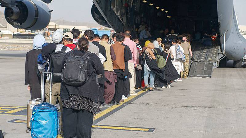 People line up to board a U.S. transport plane during the evacuation of civilians from Hamid...