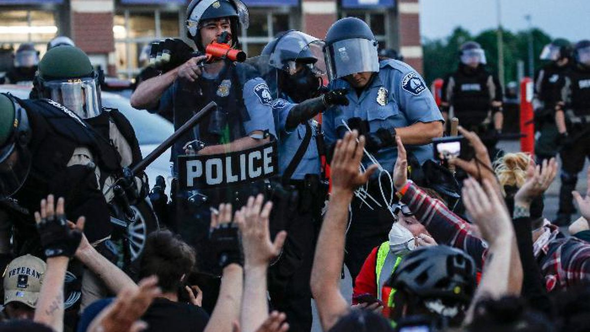 FILE - In this Sunday, May 31, 2020, file photo, a police officer points a hand cannon at protesters who have been detained pending arrest on South Washington Street, in Minneapolis. President Donald Trump has characterized those clashing with law enforcement in the wake of George Floyd's death under the knee of a Minneapolis police officer as radical-left thugs engaging in domestic terrorism. The Associated Press has found that more than 85 percent of those charged by police were locals. Only a handful appeared to have any affiliation with organized groups involved in the protests. (AP Photo/John Minchillo, File)