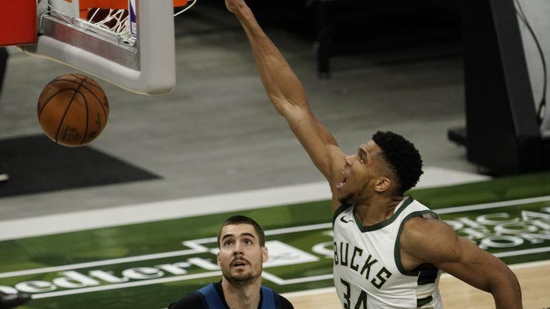 Milwaukee Bucks' Giannis Antetokounmpo dunks over Minnesota Timberwolves' Juancho Hernangomez...