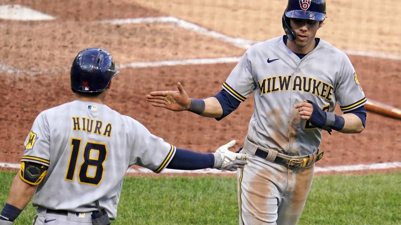 Milwaukee Brewers' Christian Yelich, right, celebrates with Keston Hiura after scoring on a...