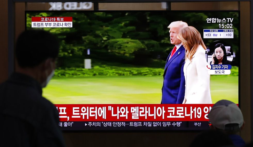 """People wearing face masks watch a TV screen reporting about U.S. President Donald Trump and first lady Melania Trump during a news program with a file footage at the Seoul Railway Station in Seoul, South Korea, Friday, Oct. 2, 2020. Trump said early Friday that he and Melania Trump have tested positive for the coronavirus, a stunning announcement that plunges the country deeper into uncertainty just a month before the presidential election. The Korean letters read: """"President Donald Trump tweeted, I and first lady Melania Trump tested positive for COVID-19."""""""
