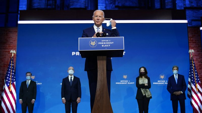 President-elect Joe Biden removes his face mask as he arrives to introduce his nominees and...