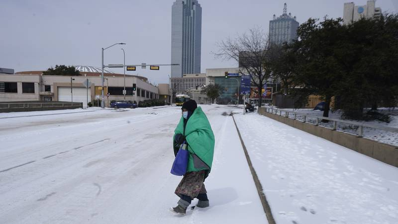 A woman wrapped in a blanket crosses the street near downtown Dallas, Tuesday, Feb. 16, 2021. ...