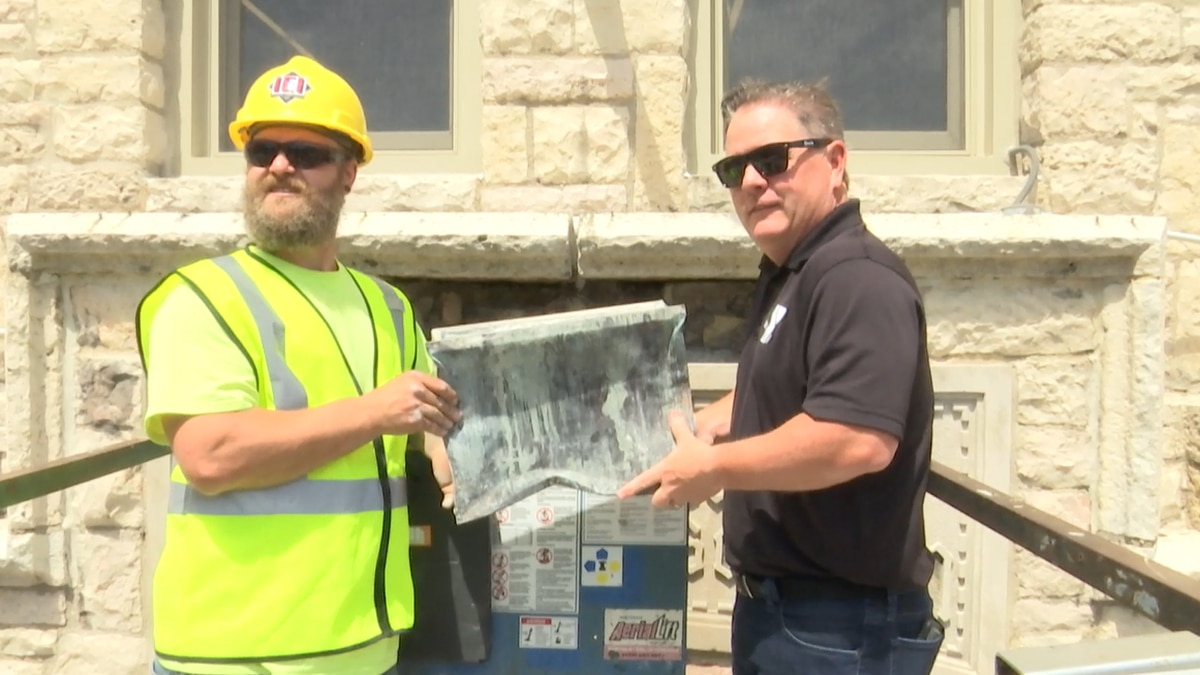 Contractors and the President of the Ferguson Family YMCA stand with the time capsule above the...