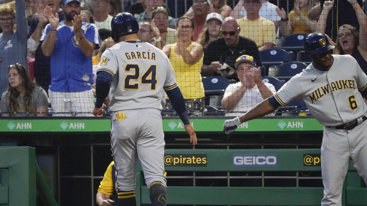 Milwaukee Brewers' Avisail Garcia (24) is greeted by Lorenzo Cain (6) after scoring on a hit by...