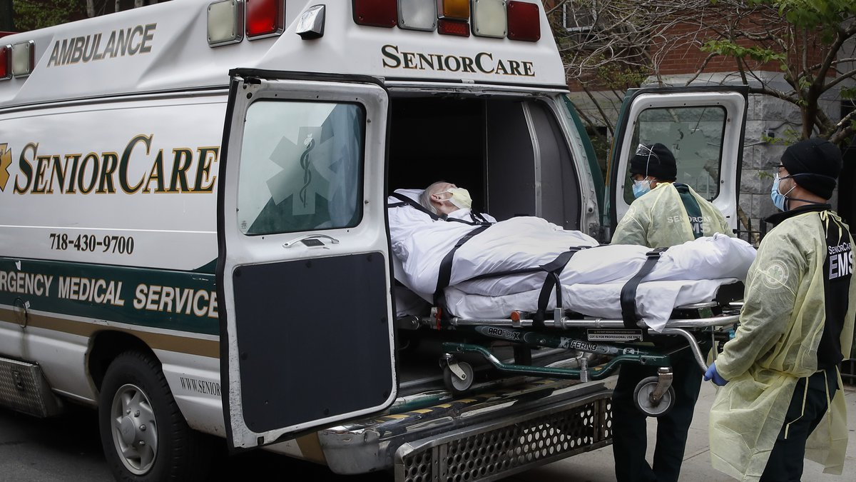 In this April 17, 2020, file photo, a patient is loaded into an ambulance by emergency medical...