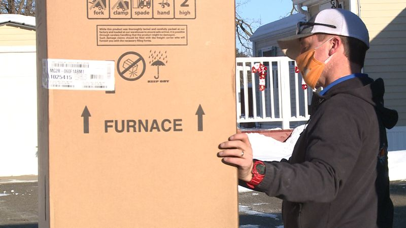 Shane Larson, owner of Under Aire Heating and Cooling installs a new furnace for a Rice Lake...