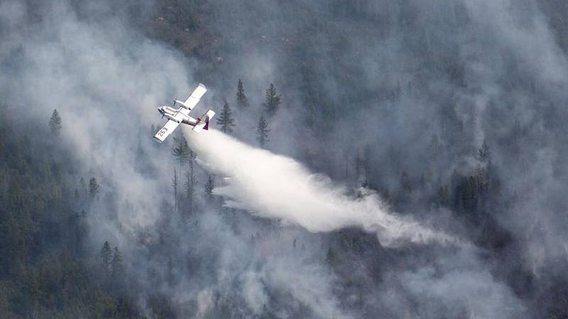 An Aircraft drops water scooped from nearby Sand Lake onto the Greenwood Fire, about 50 miles...