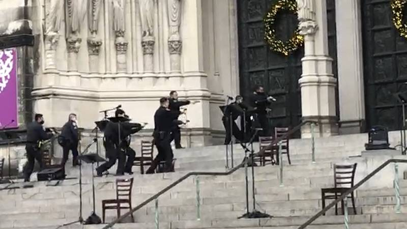 New York police officers move in on the scene of a shooting at the Cathedral Church of St. John...