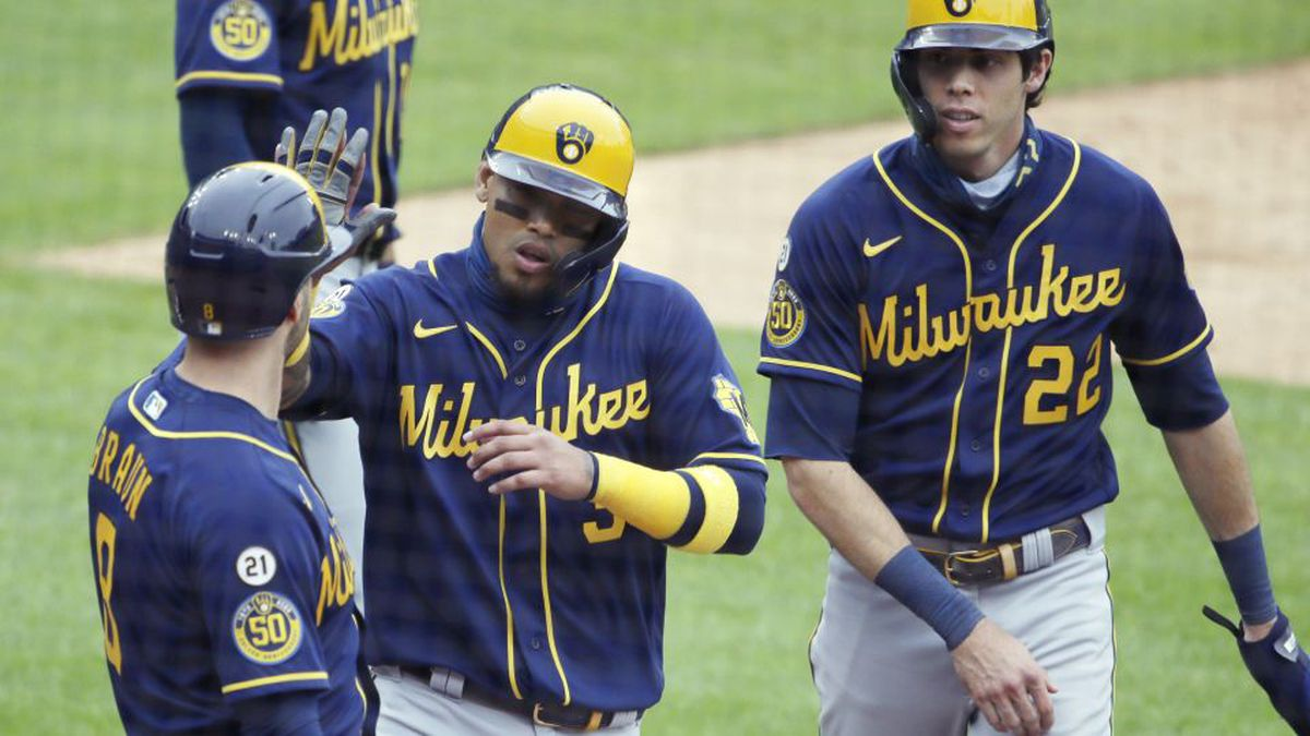 Milwaukee Brewers' Orlando Arcia, center, celebrates with Ryan Braun (8) and Christian Yelich (22) after they all scored against the Detroit Tigers on a double by Louis Arias during the sixth inning of a baseball game Wednesday, Sept. 9, 2020, in Detroit. The Brewers defeated the Tigers 19-0. (AP Photo/Duane Burleson)
