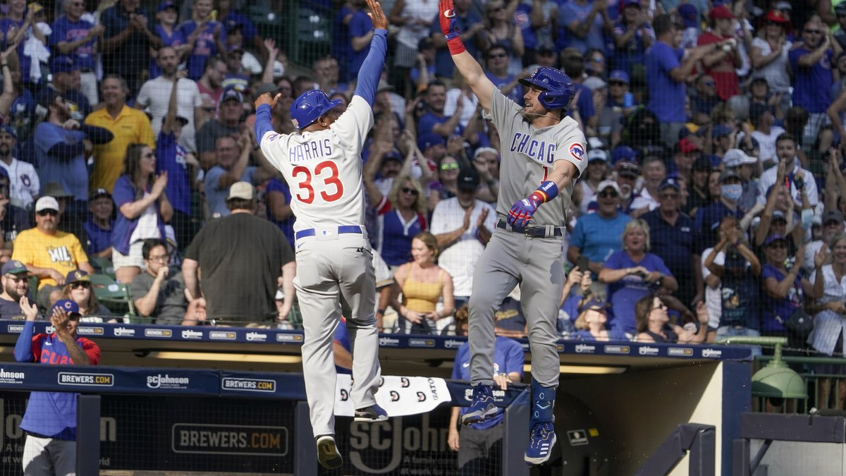 Chicago Cubs' Patrick Wisdom celebrates with third base coach Willie Harris (33) after hitting...